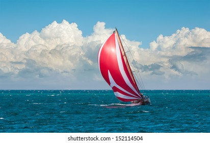 Yacht sailing at waves of the sea. Nautical landscape with sailboat - cruising yacht sailing under full sail taking part in regatta race. Yachting - maritime romantic trip on the yacht with red sails.