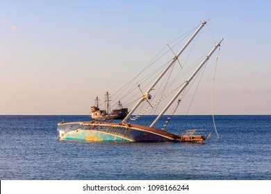 Yacht Shipwreck and Sailboat, Sunset colors. Sinking ship.
