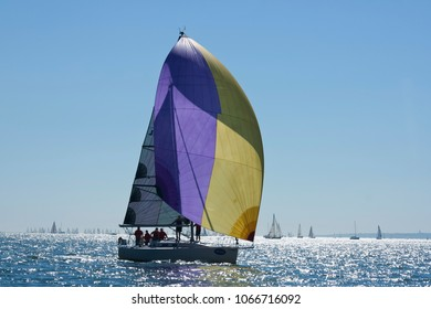 yacht silhouetted against the bright sun on the solent during cowes week race