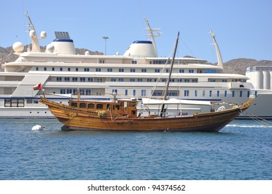 The yacht of the Sultan of Oman moored in Muscat Harbor, A traditional fishing dhow is anchored in front