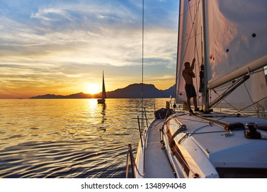 yacht at sunset. man at the mast of the boat