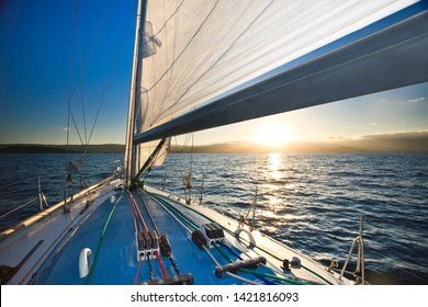 Yacht and sunset with mountains at the horizon