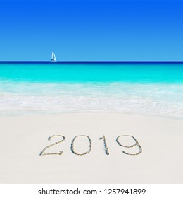 Yacht under sail in ocean water at tropical beach and happy new year 2019 season caption on sand. Tropical vacation concept. Anse Georgette, Praslin island, Seychelles