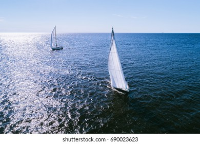 Yacht with white sails in dark blue open space, the good wind fills sails. Aerial photography captured with a drone on a sunny summer day.