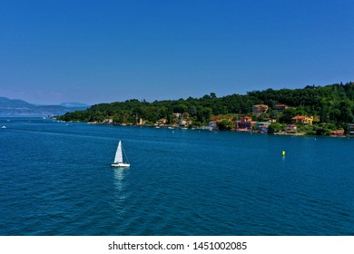 The yacht is white with white sails, quietly moving along the coastline of the small resort town of Salo Italy on Lake Garda.