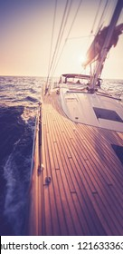 Yachting background. Yacht with wooden top at the sunset sailing at the open sea. Sailing theme, freedom of the Yachting.