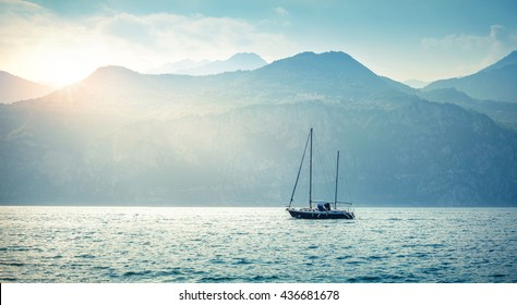 Yachting. Landscape panorama with yacht sailer ship sailing by lake or sea waves in evening sunset sun sunbeams. Fishing sporting poat on water. Mountains background. Garda Lake, Veneto region, Italy