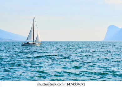 Yachting. Landscape with yacht sailer ship sailing by lake or sea waves in evening sunset sun sunbeams. Fishing sporting boat on water. Mountains background. Garda Lake, Veneto region, Italy