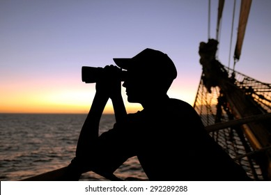Yachting. Sailing ship. A young man looking through binoculars at sunset