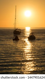 Yachts and boats on the background of a beautiful sunset with the sun setting in the sea