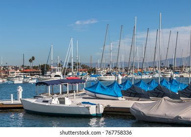 Yachts and covered sailboats docked at marina. Sky and clouds background.