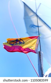 Yachts Ensign of Spain waving in the wind against blue sky background. Sunny weather.