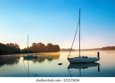 Yachts float on the calm waters of the lake. Early morning. Masuria, Poland .