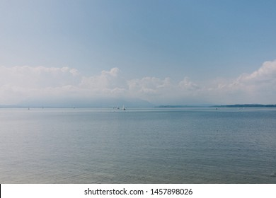 Yachts floating on blue lake Chiemsee against cloudy sky and mountains during sunny day