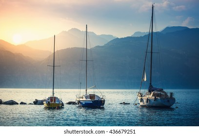 Yachts. Landscape panorama, sailer boats ships sailing lake or sea waves, evening sunset sun sunbeams. Sport yachting or fishing. High mountains background. Malcesine, Garda Lake, Veneto region, Italy