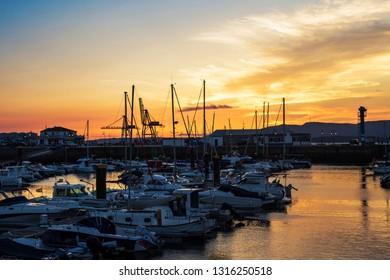 Yachts moored at the dock of the Vilagarcia de Arousa marina at golden dusk