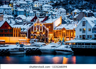 Yachts moored in harbour of Bergan, Norway. Brightly lighted houses near port of Bergan during Christmas