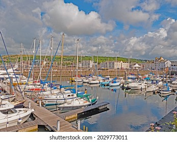 Yachts moored in Whitehaven marina against a background of cumulous clouds