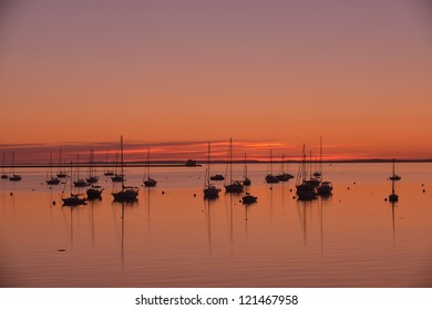 Yachts and sailboats anchored in Rockland Harbor with the Rockland Breakwater Lighthouse in the background at sunrise