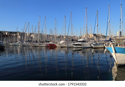 Yachts and sailboats and their reflections in the old port of Marseille, France