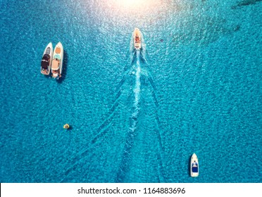 Yachts at the sea in Balearic islands, Spain. Aerial view of luxury floating boat in transparent blue water at sunset. Summer landscape. Top view from drone. Seascape with motorboat in bay. Travel