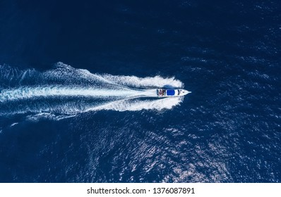 Yachts at the sea in Bali, Indonesia. Aerial view of luxury floating boat on transparent turquoise water at sunny day. View from drone. Seascape with motorboat in bay. Travel - image
