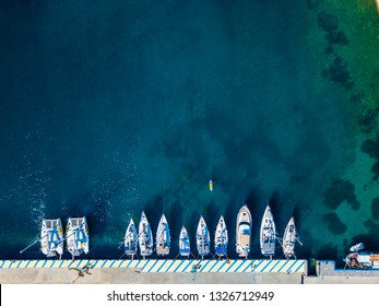Yachts at the sea in Greece. Aerial view of floating boat on transparent turquoise water at sunny day. Summer seascape from air. Top view from drone. Travel concept and idea