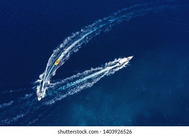 Yachts at the sea surface. Aerial view of luxury floating boat on transparent turquoise water at sunny day. Top view from drone. Seascape with motorboat in bay. Travel - image