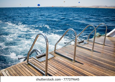 yacht's stern with two boarding ladders on a background of azure sea. great vacation. amazing summer day in open water on a boat.