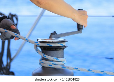Yachtsman hands dealing with yacht ropes on halyard winch