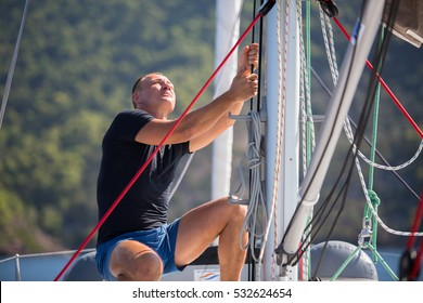 Yachtsman pulls the rope controlling the sail on sailing boat.