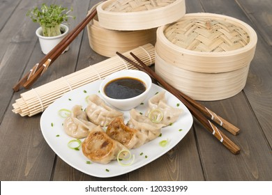 Yaki-Gyoza - Japanese pan-fried dumplings served with a soy based dipping sauce. Dark wood background.
