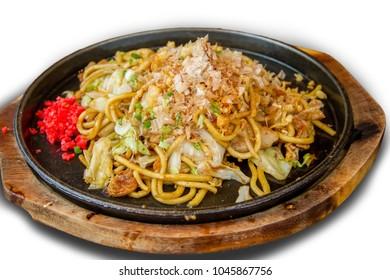Yakisoba a Japanese noodle stir-fry dish on iron pan with white isolated background