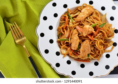 Yakisoba.Japanese famous foods.Stir-fried noodles with chicken and vegetables with copy space for design work.Enjoy eating.Happy meal.Simple cooking with delicious menu at home.Green background