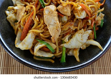 Yakisoba.Japanese famous foods.Stir-fried noodles with chicken and vegetables with copy space for design work.Enjoy eating.Happy meal.Simple cooking with delicious menu at home.Wooden background