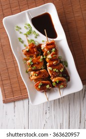 Yakitori chicken with green onions on a plate on the table. vertical top view