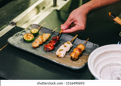 Yakitori (Japanese-Style Grilled Chicken Skewers) with chicken, internal organ and cucumber served on black stone plate with hand pinching.