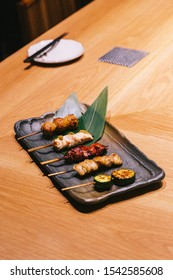 Yakitori (Japanese-Style Grilled Chicken Skewers) with chicken, internal organ and cucumber served on black stone plate.
