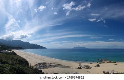 Yakushima coast panorama on sunny day, turquoise sea water, sandy beach, blue sky, distant Kuchierabujima isalnd
