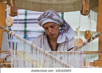 Yakushyntsi, Ukraine - 22.06.2019: portrait of woman weaver working at ancient loom, making carpet at Live Fire Midsummer Pagan Ethnofestival
