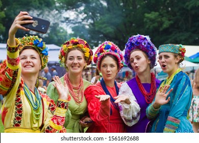 Yakushyntsi, Ukraine - 22.06.2019: young beautiful girls make a selfie with a smartphone, wear retro style clothes, shirts, blouses, embroidery, necklaces and shawls, Living Fire Pagan Ethno festival