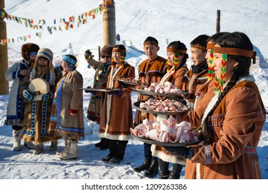 Yakutsk, Republic of Sakha (Yakutia)/Russia - March 01 2015: young Yakuts in national folk clothes holding wood Yakut utensils with traditional food - sliced planed fish and meat (stroganina)