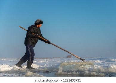 Yakutsk, Republic of Sakha (Yakutia)/Russia - November 03 2014: an elderly man harvesting ice on a frozen lake. Traditional ice harvesting for the winter