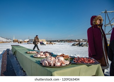 Yakutsk, Republic of Sakha (Yakutia)/Russia-March 01 2015: young Yakut woman next to a table with siberian traditional food-sliced frozen white fish and meat (stroganina). Festival Meeting of the Sun