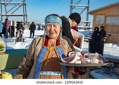 Yakutsk, Republic of Sakha (Yakutia)/Russia-March 01 2015: Yakut old woman in national clothes with siberian traditional food-sliced frozen raw white fish (stroganina). Festival Meeting of the Sun