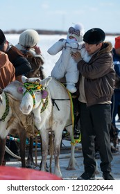 Yakutsk, Republic of Sakha (Yakutia)/Russia-March 18 2017: father put his baby on a white stag at the festival of reindeer herders