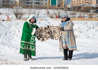 Yakutsk, Republic of Sakha (Yakutia)/Russia-March 18 2017: Yakut women in traditional clothes holding fur decorative rugs at the festival of reindeer herders