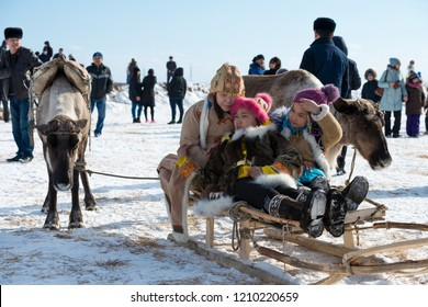 Yakutsk, Republic of Sakha (Yakutia)/Russia-March 18 2017: Yakut girls in national clothes sitting on sledges at the festival of reindeer herders