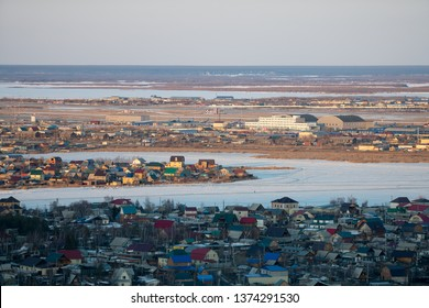 Yakutsk, Yakutia / Russia - April 14 2019: Yakutsk city downtown aerial view from hill at amazing sunset. Aerial view of Yakutsk skyline with Beloe lake in beautiful post sunset