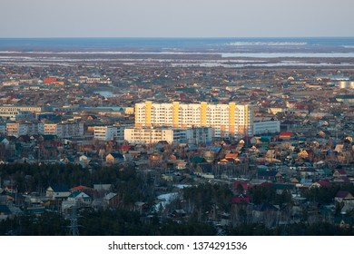 Yakutsk, Yakutia / Russia - April 14 2019: Yakutsk city downtown aerial view from hill at amazing sunset. Sunrise or sunset overlooking the new buildings of the city